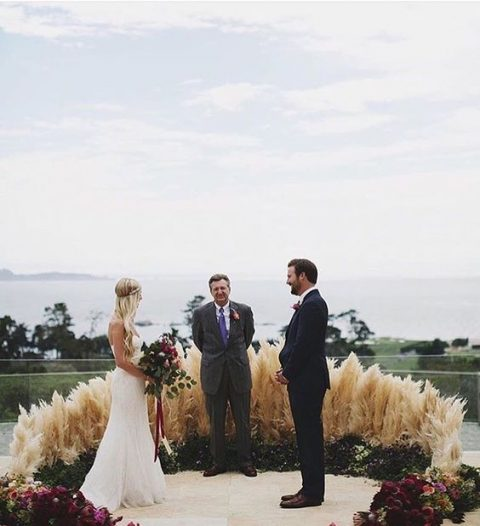 a semi circular wedding altar of grass, pampas grass and burgundy blooms