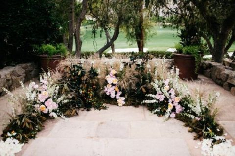 a textural wedding altar of various herbs, leaves, blush and white blooms