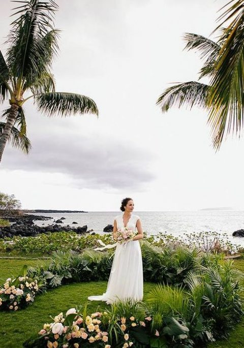 a tropical semi circular wedding arch of blush flowers and tropical leaves