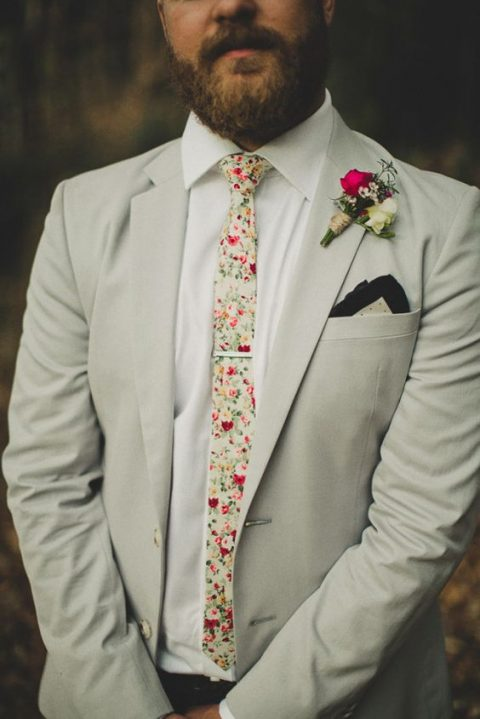 an off-white suit, a white shirt and a floral tie plus a bright boutonniere