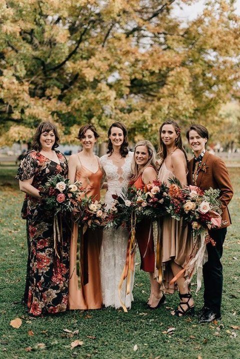 mismatched bridesmaids_outfits including silk gowns in blush and orange, a floral maxi dress and a pantsuit with a floral shirt