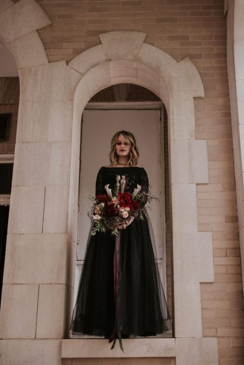 a bateau neckline black wedding gown with a lace bodice and a layered skirt