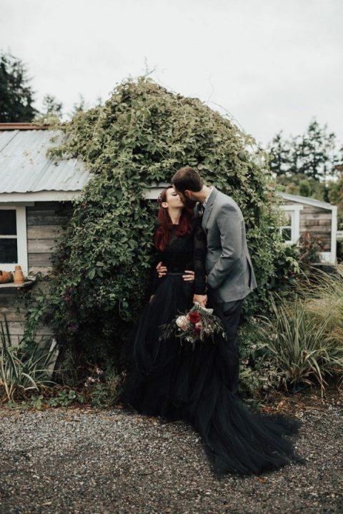 a beautiful black wedding dress with a lace bodice with long sleeves and a layered tulle skirt with a train