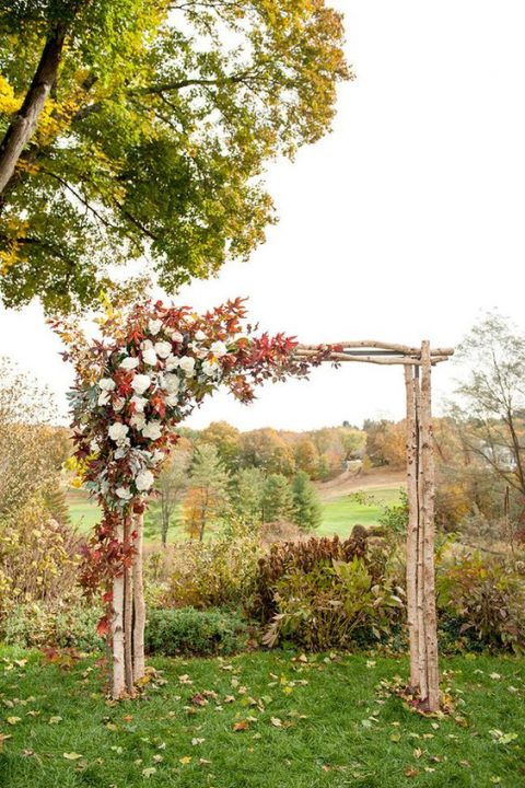 a birch branch wedding arch decorated with fall foliage and white blooms
