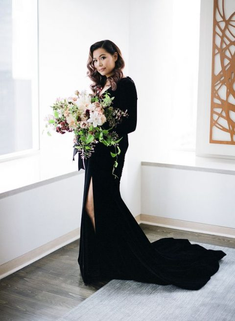 a black velvet wedding dress with a side slit, a train, a deep V-neck and long sleeves