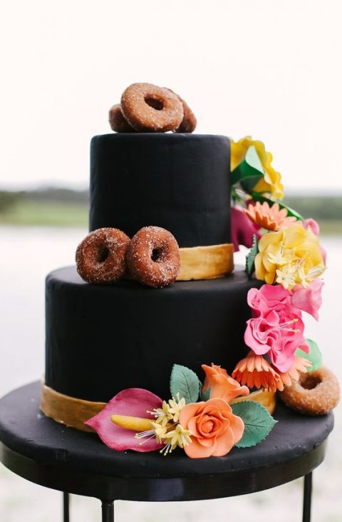 a black wedding cake topped with sugar blooms and fall-spiced donuts