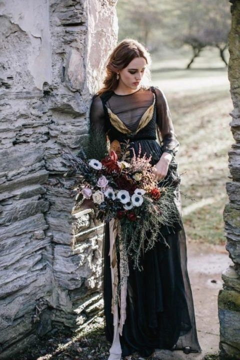 a black wedding dress with an illusion bodice and sleeves, gold detailing and a layered skirt