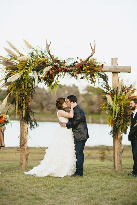 a boho chic fall arch adorned with anntlers, pampas grass and fall blooms