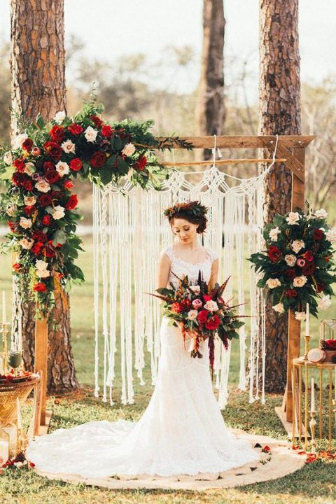 a boho wedding arch adorned with macrame, greenery, blush and red roses