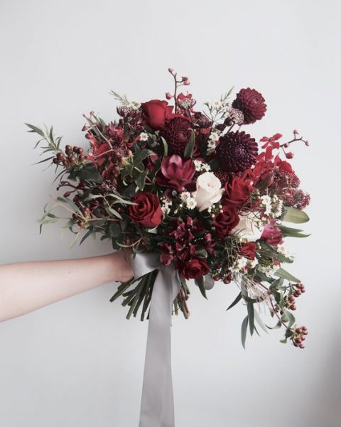 a bold fall bouquet in deep red and burgundy, with berries and greenery