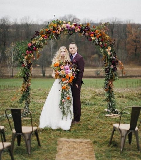 a bold fall wedding arch with greenery, fall leaves, bright blooms in orange, purple and yellow