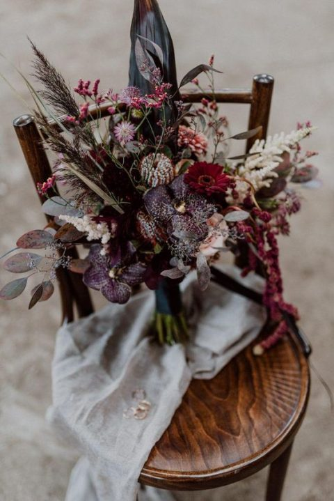 a bold fall wedding bouquet with burgundy, deep purple blooms and various herbs and foliage