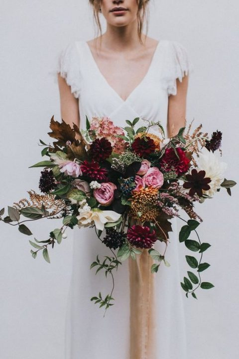 a bold fall wedding bouquet with plum, pink, deep purple blooms and cascading greenery
