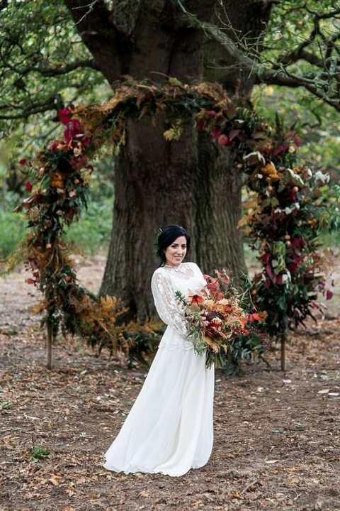 a bold fall wedding woodland wedding arch with leaves, greenery and blooms