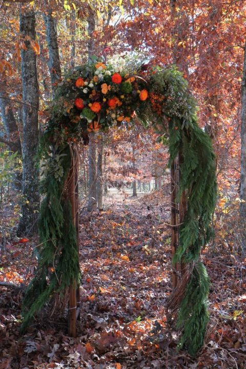 a bold fall woodland arbor with fir branches and bold blooms