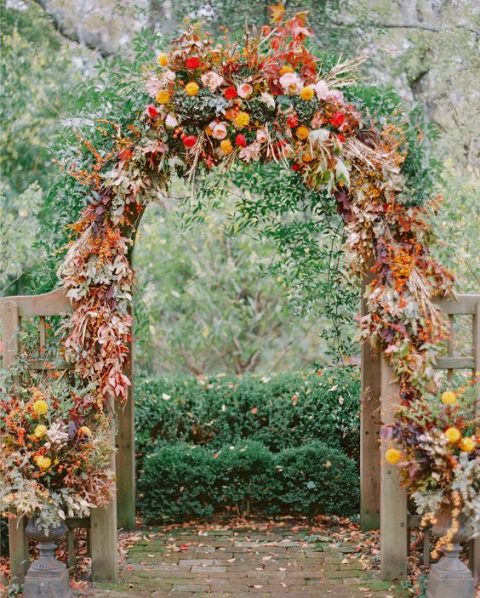 a bright and colorful wedding arch with orange, yellow, red and fall foliage