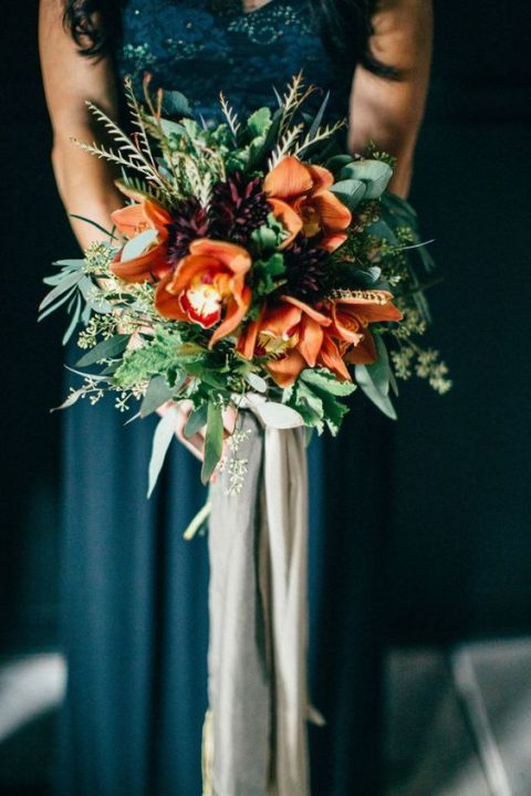 a bright fall wedding bouquet with orange, deep purple blooms and textural greenery