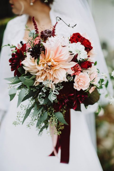 a bright fall wedding bouquet with red, burgundy and blush flowers plus greenery