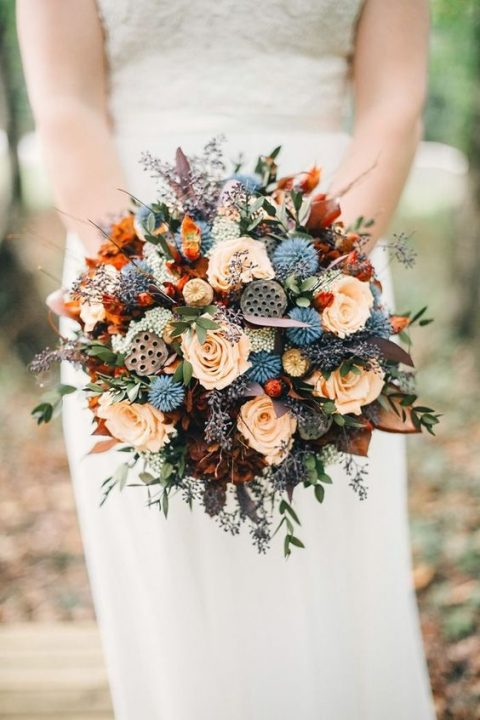 a bright wedding bouquet with blue, orange and peachy blooms and much texture