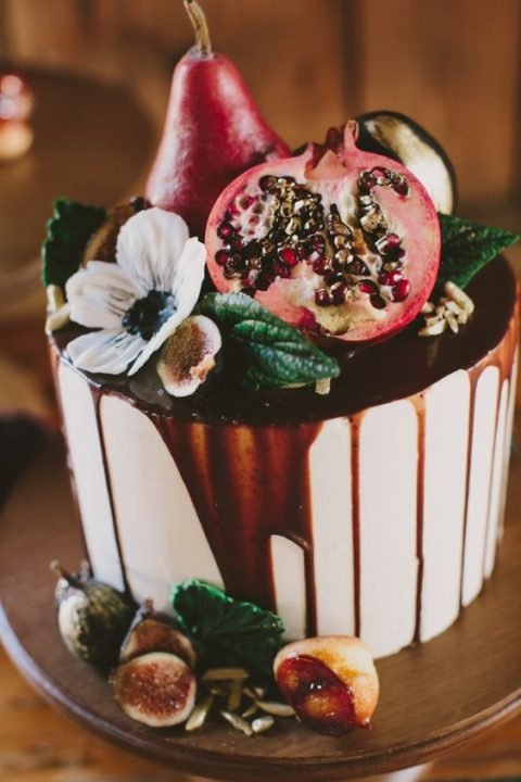 a buttercream wedding cake with chocolate drip, pomegranates, pears and blooms