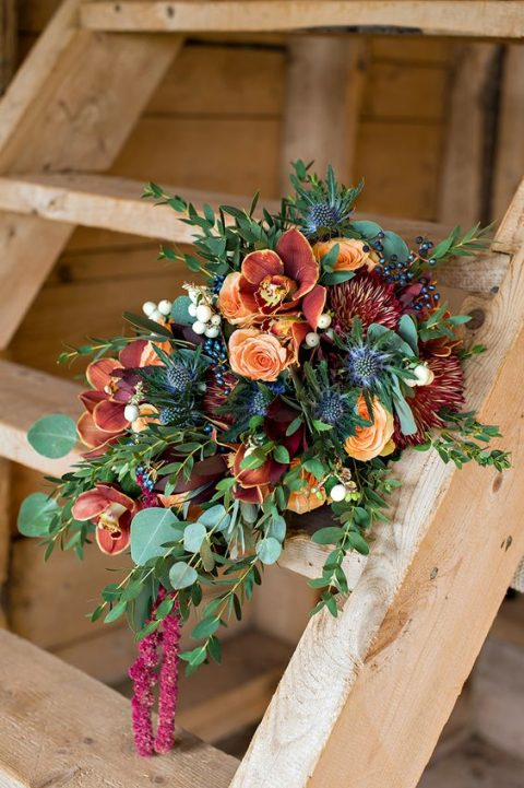 a cascading fall wedding bouquet in the shades of rust, orange and plum