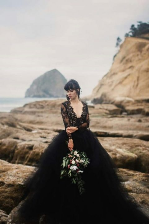 a chic black wedding dress with a lace bodice with long sleeves and a layered tulle skirt