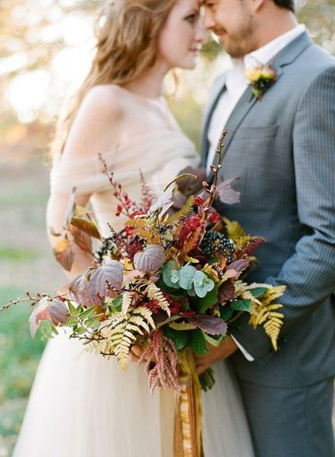 a chic fall woodland wedding bouquet with fall leaves, berries and branches