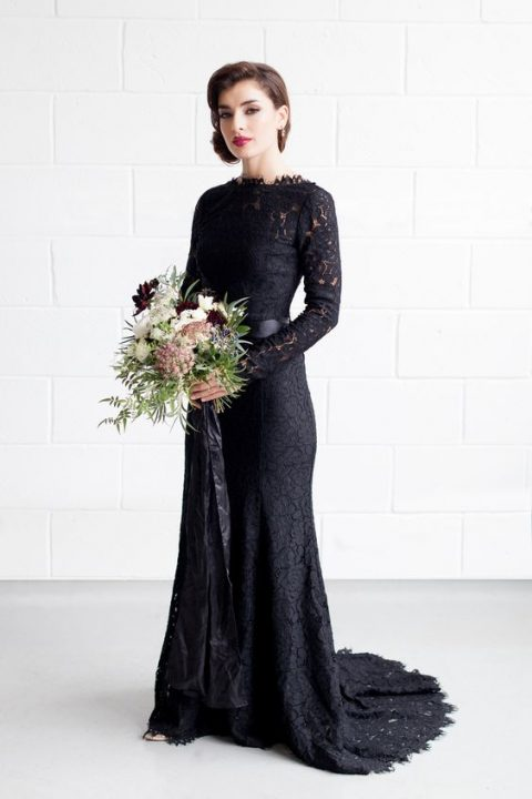 a chic sheath black lace wedding dress with long sleeves and an illusion neckline plus a train and a sash