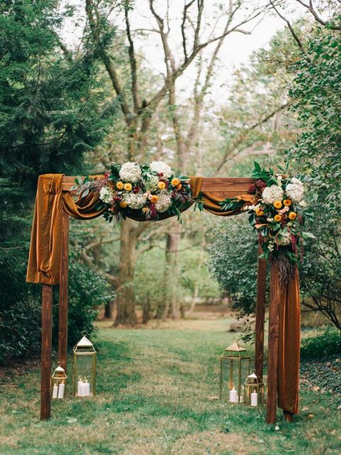 a chic wedding arch with mustard velvet fabric, orange and white blooms ad greenery