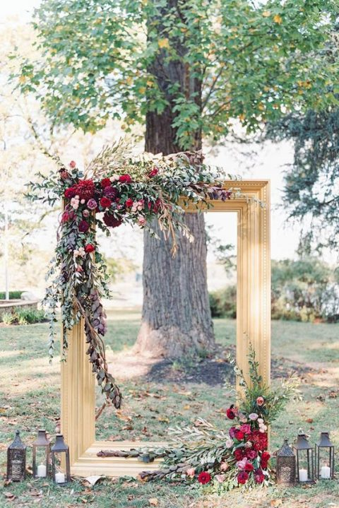 a chic wedding backdrop of an oversized gilded frame topped with foliage and burgundy and plum flowers