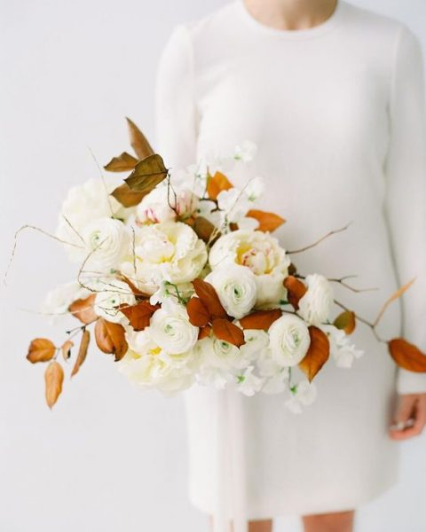 a chic wedding bouquet with white blooms and fall leaves