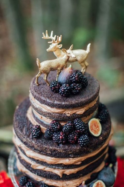 a chocolate naked wedding cake with figs and blackberries plus a deer topper