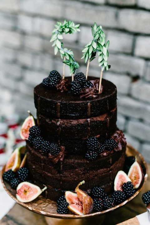 a chocolate wedding cake with blackberries, figs and greenery