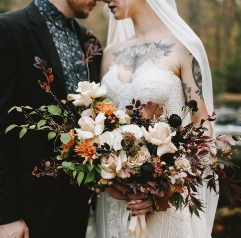a contrasting fall wedding bouquet with cream, orange and black blooms, fall leaves and berries