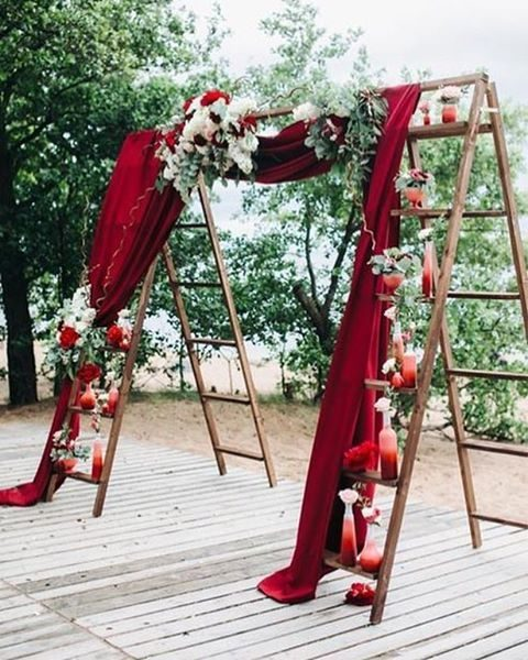 a cool fall wedding arch made of ladders, ombre painted bottles as vases and burgundy fabric