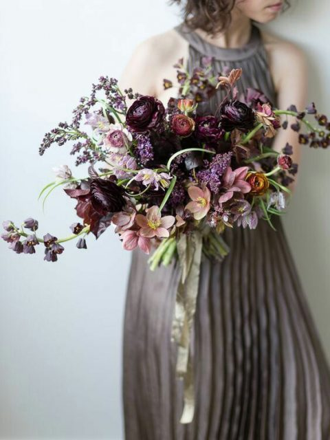 a dark wedding bouquet with deep purple and dusty pink blooms and rust touches