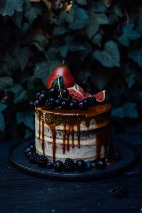 a decadent semi naked wedding cake with caramel drip, berries, pears and figs on top