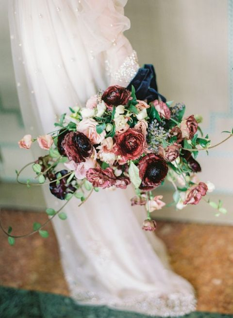 a decadent wedding bouquet with blush and burgundy blooms with greenery