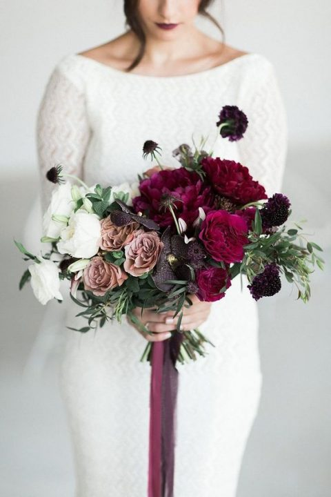 a dramatic ombre wedding bouquet from white to deep purple with bold ribbons