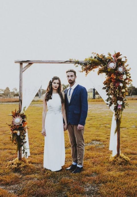 a fall boho wedding arch with white fabric, king proteas, dark foliage