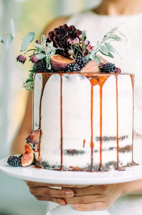a fall semi naked wedding cake with drip, blackberries and figs on top