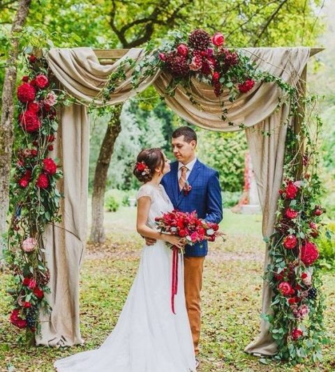 a fall wedding arch done with neutral fabric, lush greenery and deep red and burgundy blooms