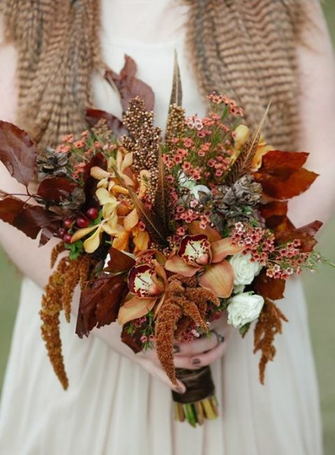 a fall wedding bouquet done in the shades of brown and rust plus feathers