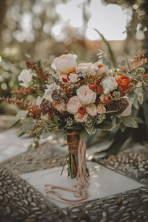 a fall wedding bouquet with blush and white blooms, herbs and greenery plus berries