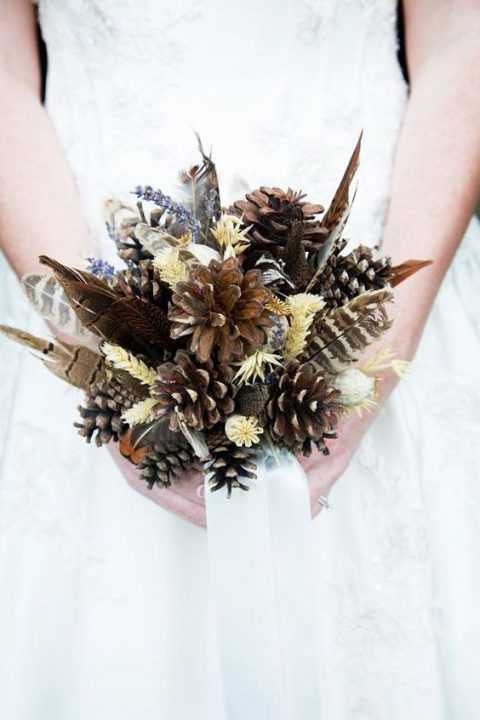 a fall wedding bouquet with feathers, pinecones and herbs