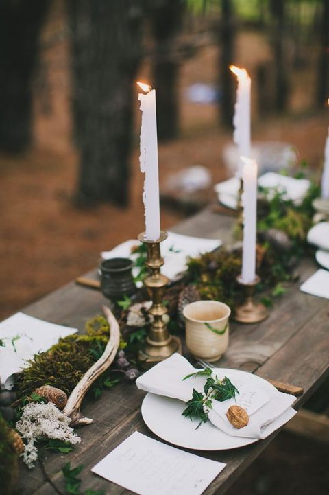 a fall woodland tablescape done with a moss runner, pinecones, antlers and nuts