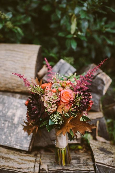a fall woodland wedding bouquet with fall leaves, dahlias and hydrangeas