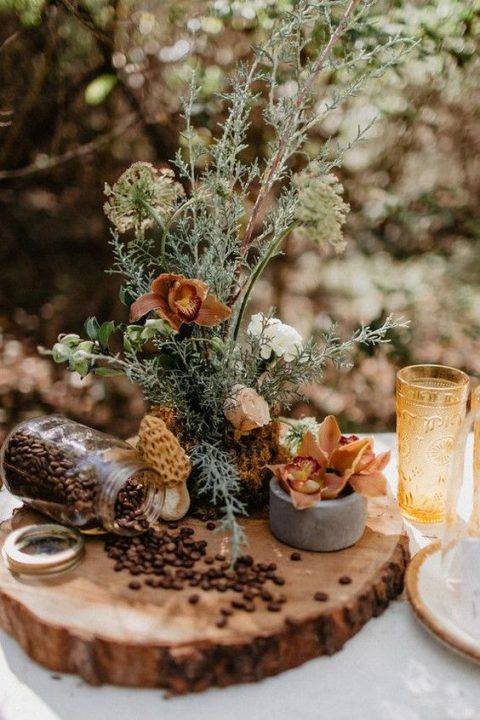 a fall woodland wedding centerpiece with herbs, coffee beans and moody blooms