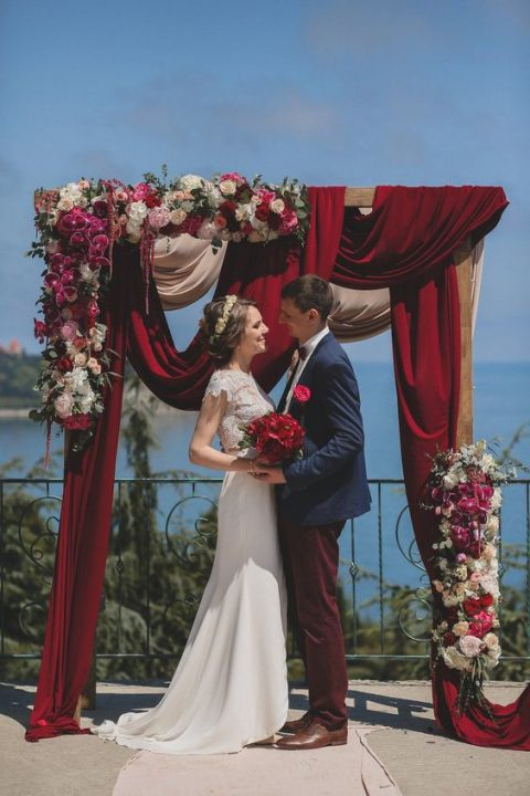 a gorgeous wedding arch done with burgundy fabric, lush white, fuchsia and burgundt florals