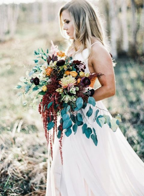 a gorgeous wedding bouquet with greenery and cascading blooms, purple and rust flowers